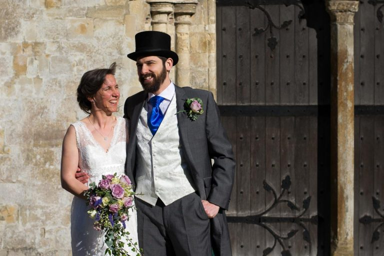 bride with bouquet and groom with top hat standing outside church doors