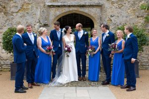 bridal party wearing blue chatting with bride and groom outside