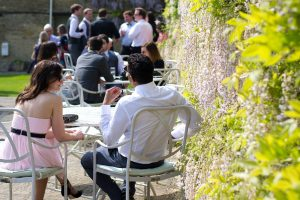 wedding guests in a garden next to white wysteria