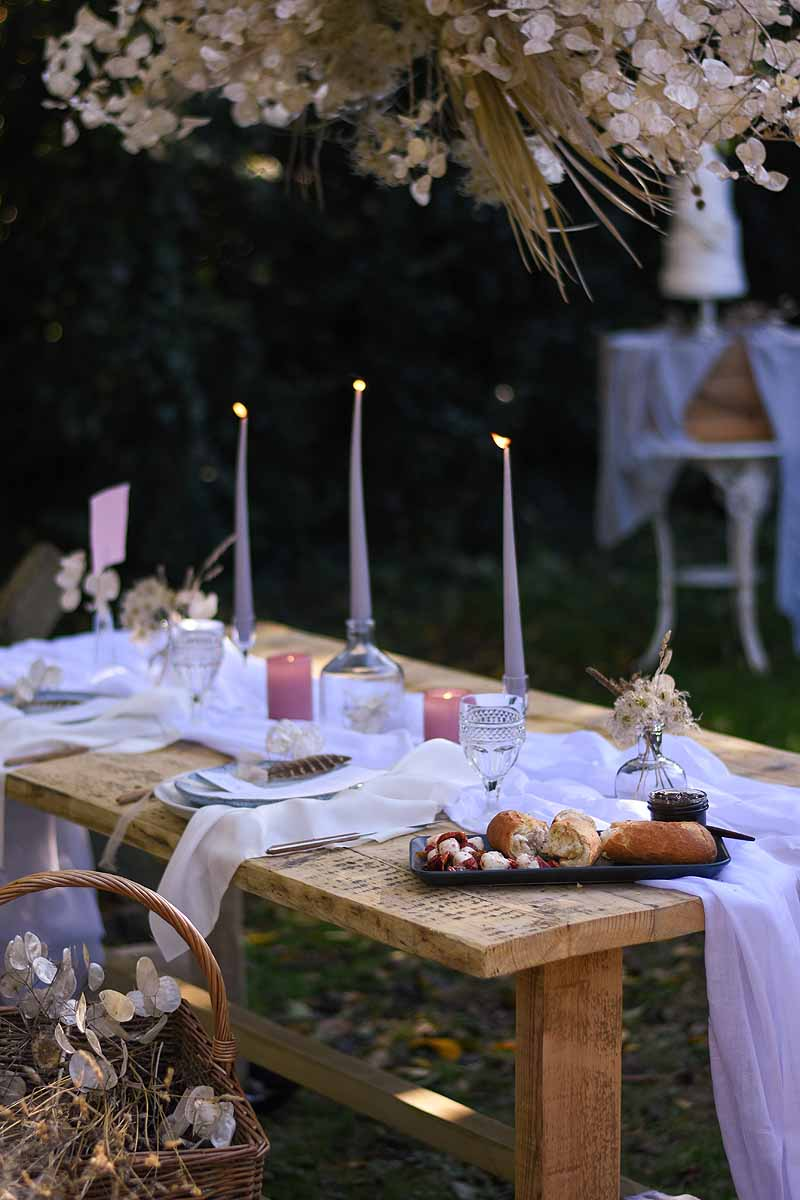 table setting outside with three candles and dried flower canopy above