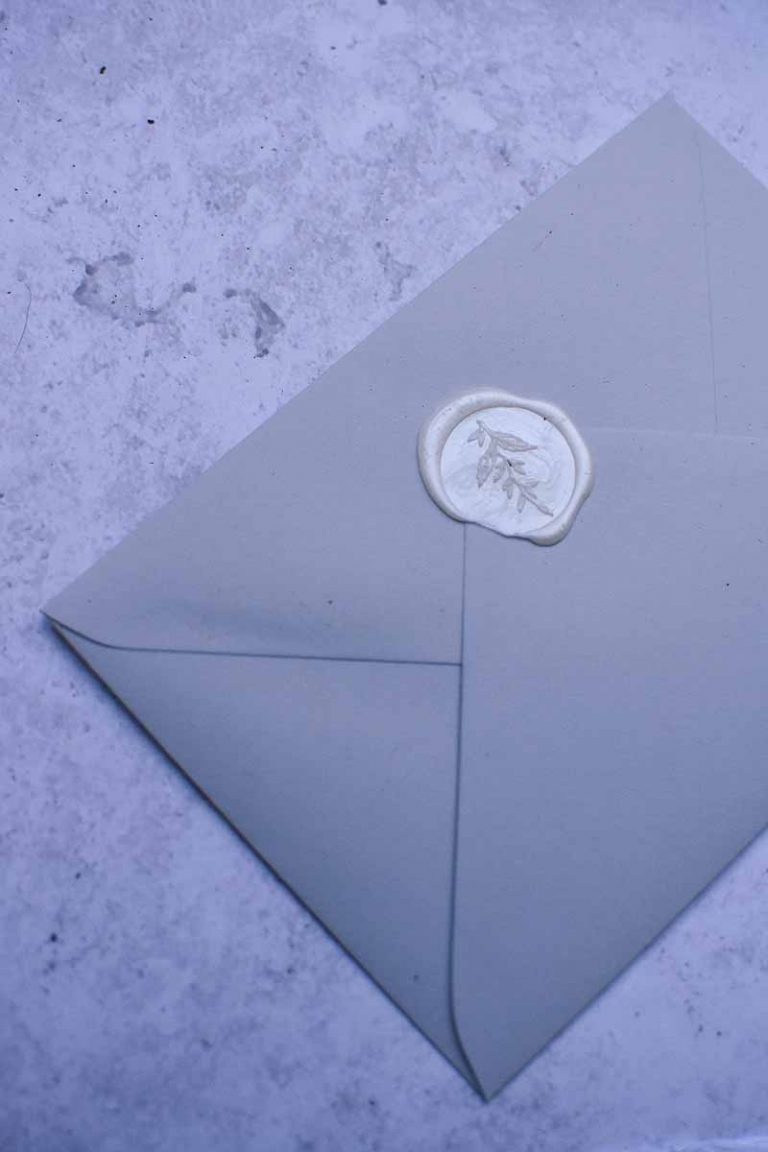 blue envelope with white wax seal on marble