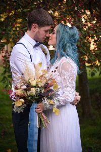 bride and groom in an autumn garden with eyes shut