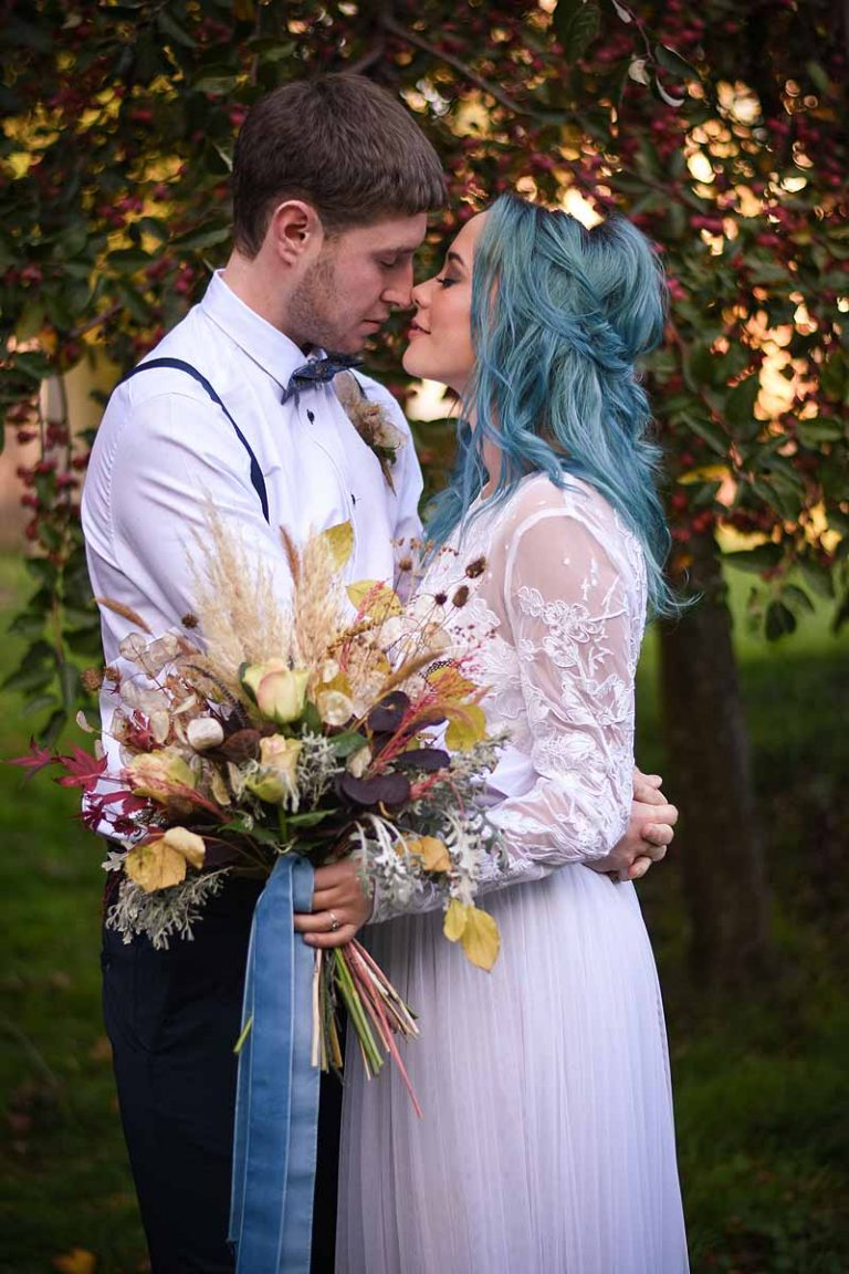 bride and groom in an autumn garden with eyes shut