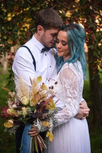 bride with blue hair looking down at autumn wedding bouquet