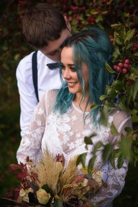 bride and groom among red berries