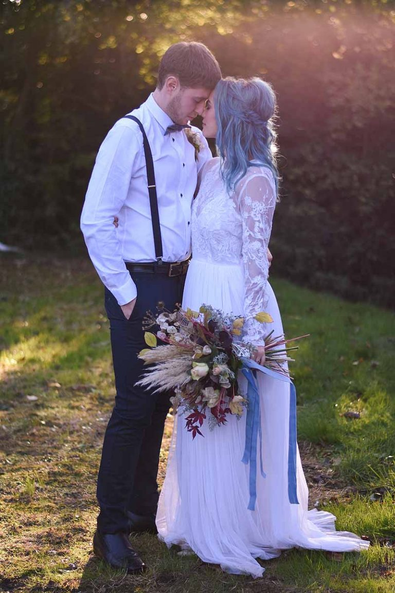 bride and groom resting their foreheads together while standing in a garden bathed in golden light