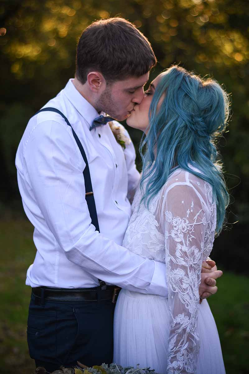 groom kissing bride with blue hair