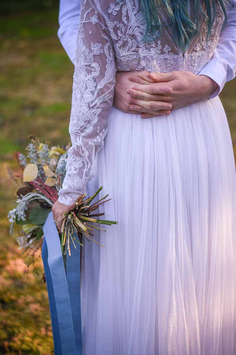 clasped hands round a bride in a white lace dress