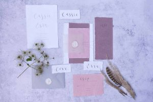 pink, purple and white wedding stationery with dried flowers and feathers