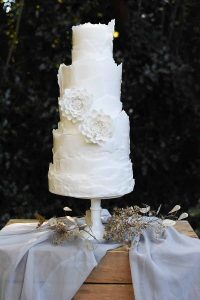 white three tier wedding cake with raw edged icing