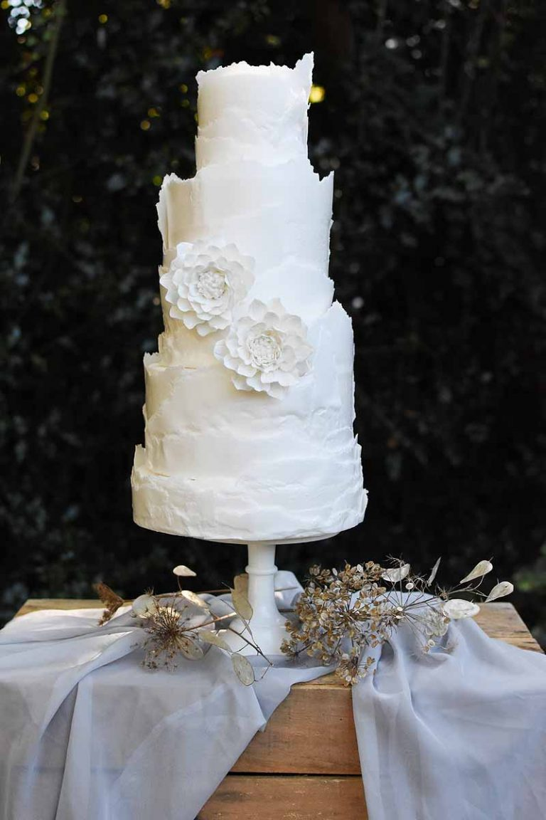 white three tier wedding cake with raw edged icing