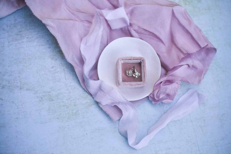 diamond stud earrings in a white dish and pink ribbons