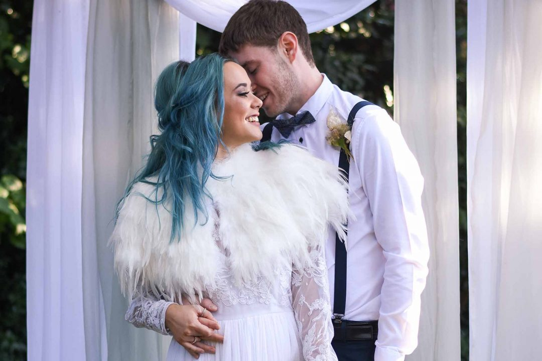Bride with blue hair and groom under white curtain