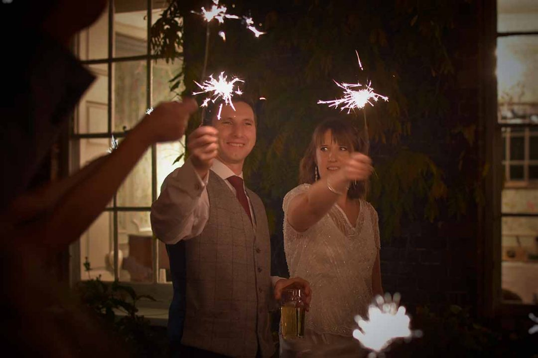 Bride and groom with sparklers outside Gildredge Manor, Eastbourne