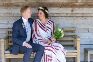 bride in red and white dress with groom in blue suit sitting on a wooden bench