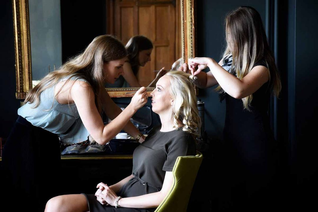 Bride having her hair and makeup done for her wedding day , Eynsham Hall, Oxfordshire