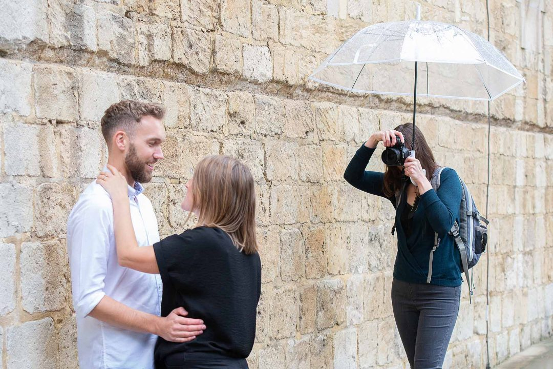 photographer with umbrella taking a photo of a couple