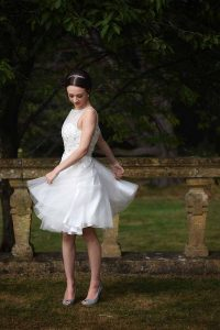 bride twirling in a knee-length bridal gown
