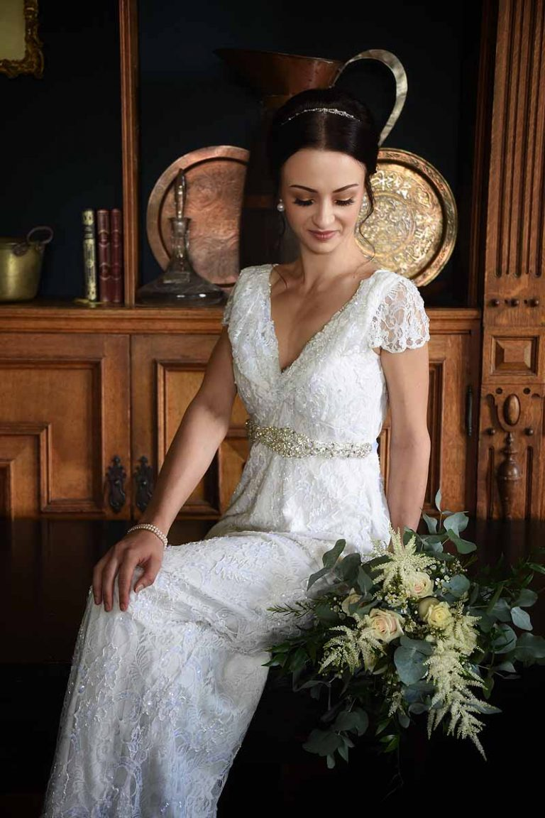 seated bride in lace dress looking down at flowers