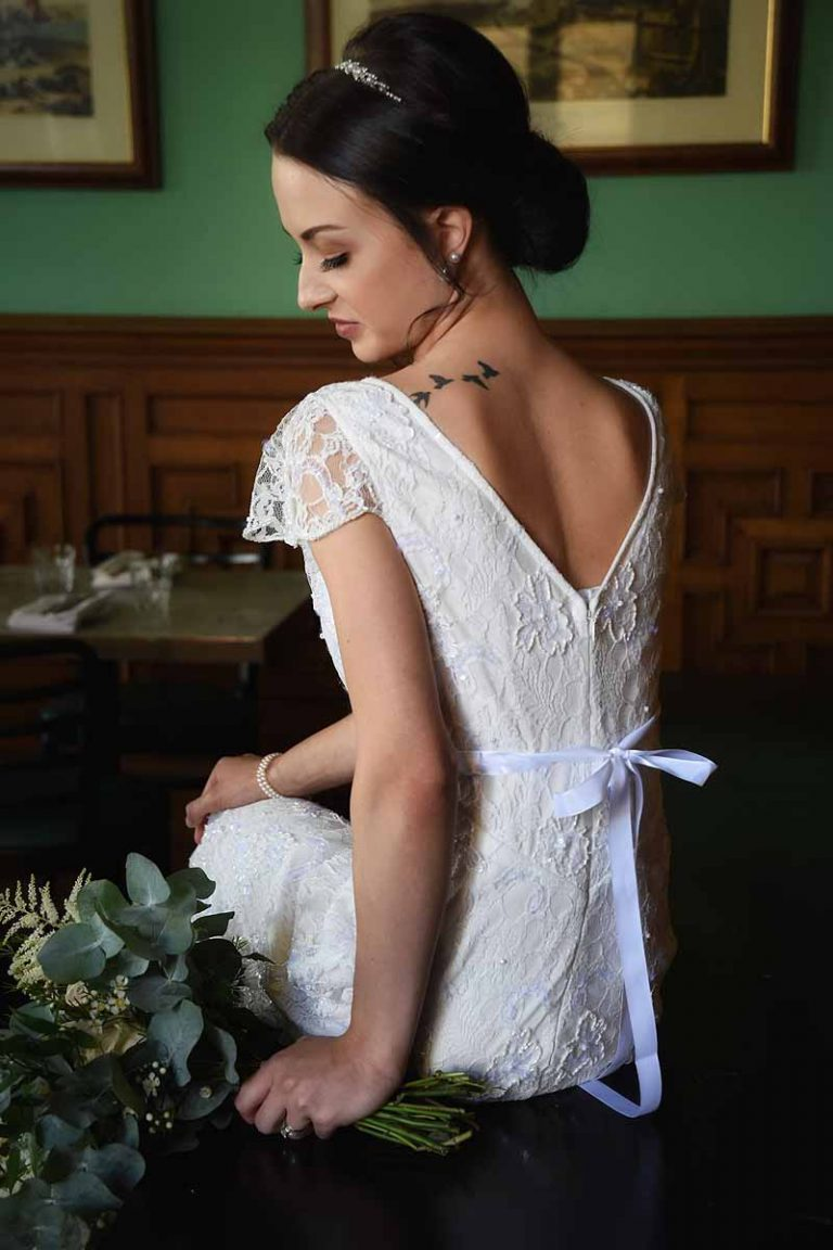 bride with bird tatoo looking down and flowers
