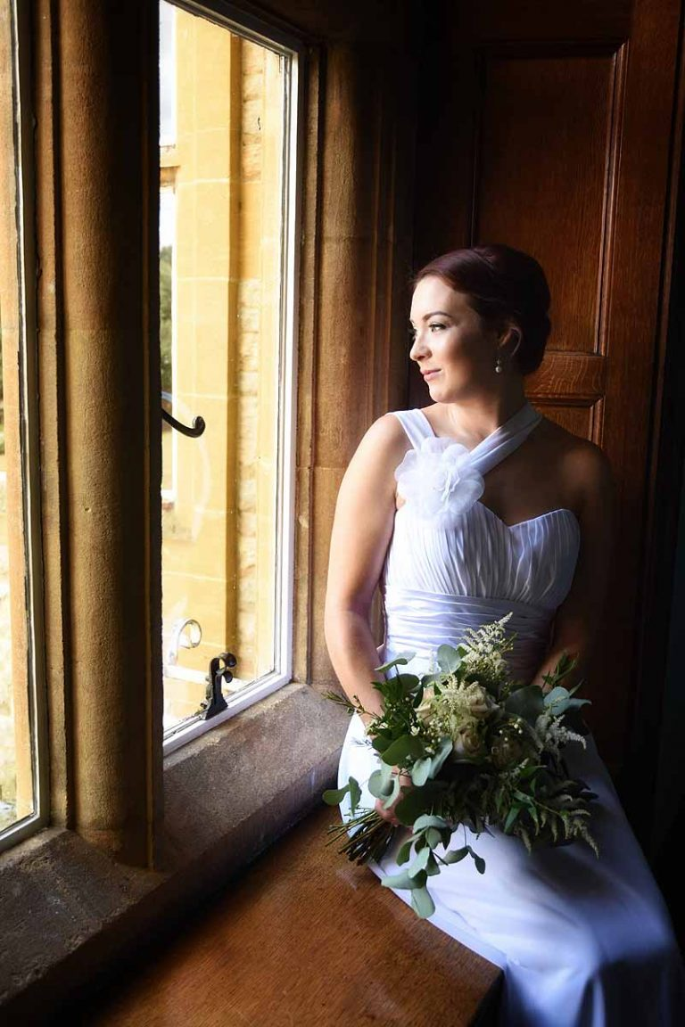 bride sitting on a window seat looking out the window
