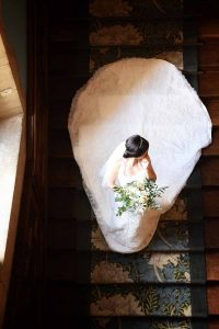 bride in dress with long train going down stairs