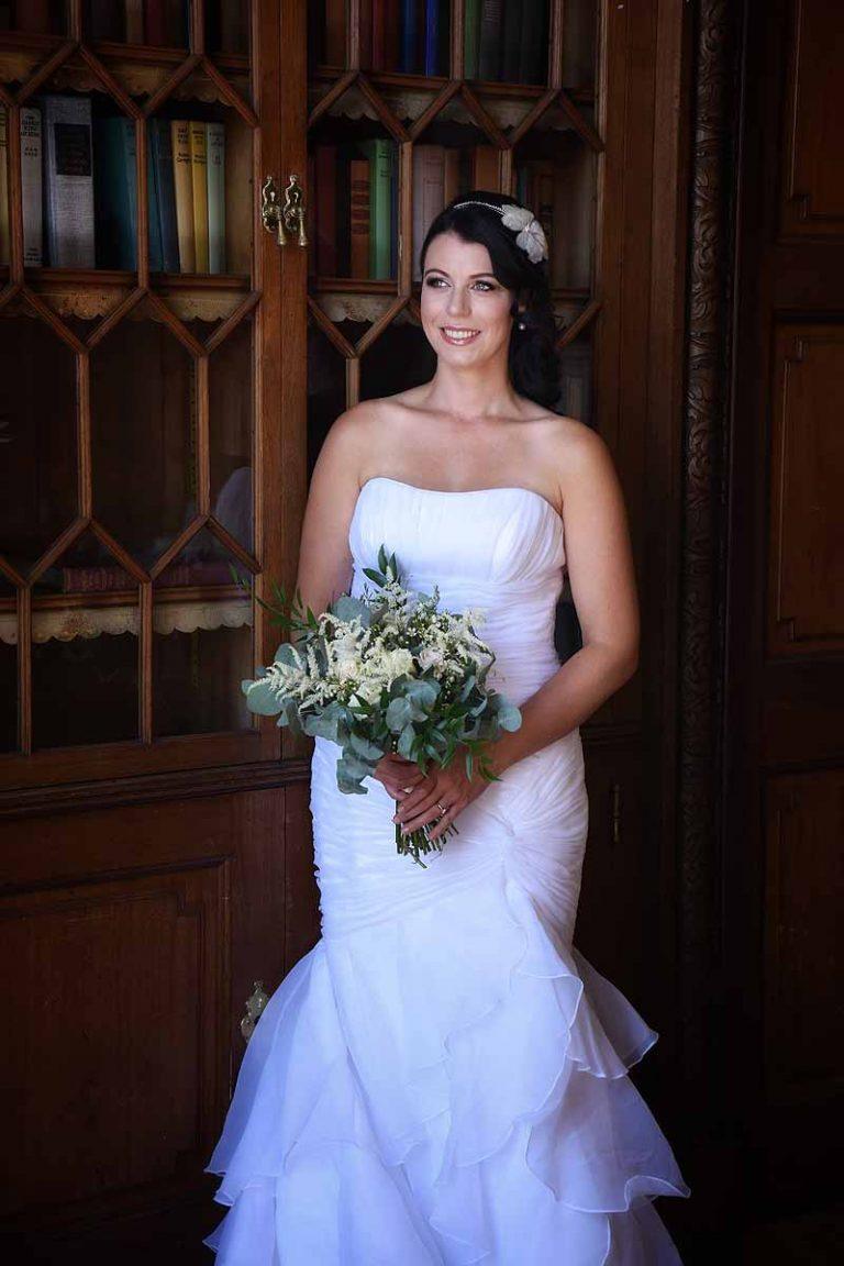 bride standing in front of bookcase