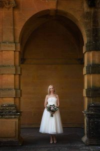 bride standing in archway of Eynsham Hall, Oxfordshire