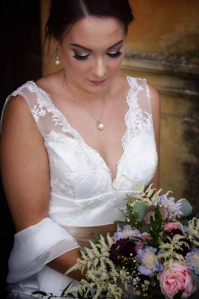 bride in lace gown with pearl jewellery holding bouquet