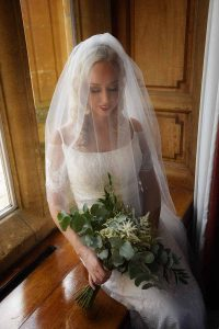 bride sitting on window seat with veil over face and holding bouquet