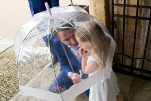 father and flower girl under a clear umbrella