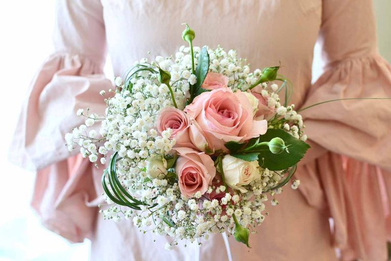 pink roses and white gypsophila bridal bouquet being held by lady in pink dress