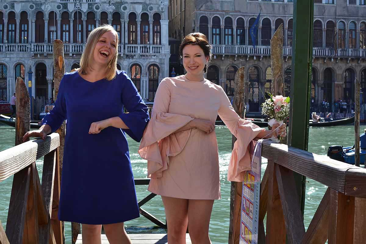 bride and guest on banks of the grand canal in Venice
