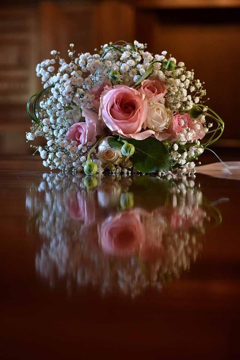 pink roses and white gypsophila bouquet reflected in shiny mahogany table