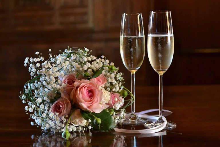 two champagne flutes next to bouquet with pink roses and white gypsophila