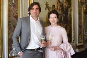 bride and groom holding champagne flutes in front of baroque fresco