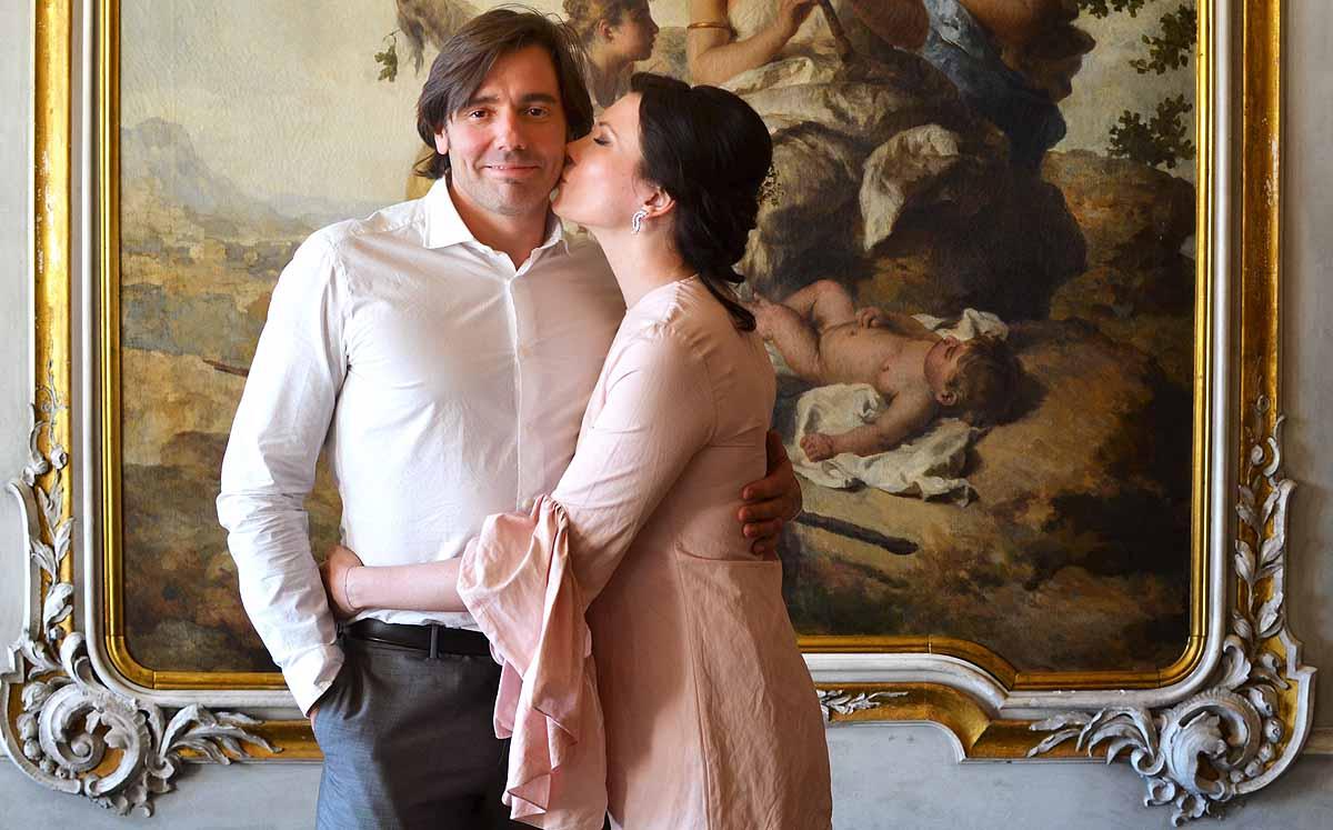 Bride in pink kissing groom in front of baroque fresco