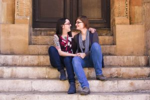 couple sitting on steps at Sheldonian Theatre Oxford