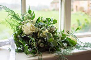 White rose and green foliage wedding bouquet on windowsill