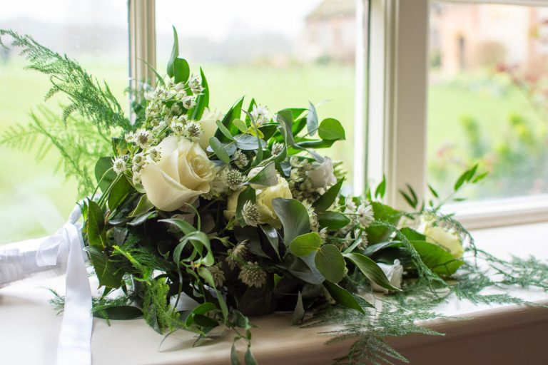 White rose and green foliage wedding bouquet on windowsill