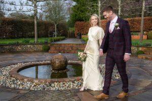 Couple walking around the fountain in the sunken garden at Bradfield College Berkshire