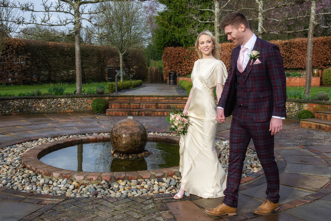 Couple walking around the fountain in the sunken garden at Bradfield College Berkshire