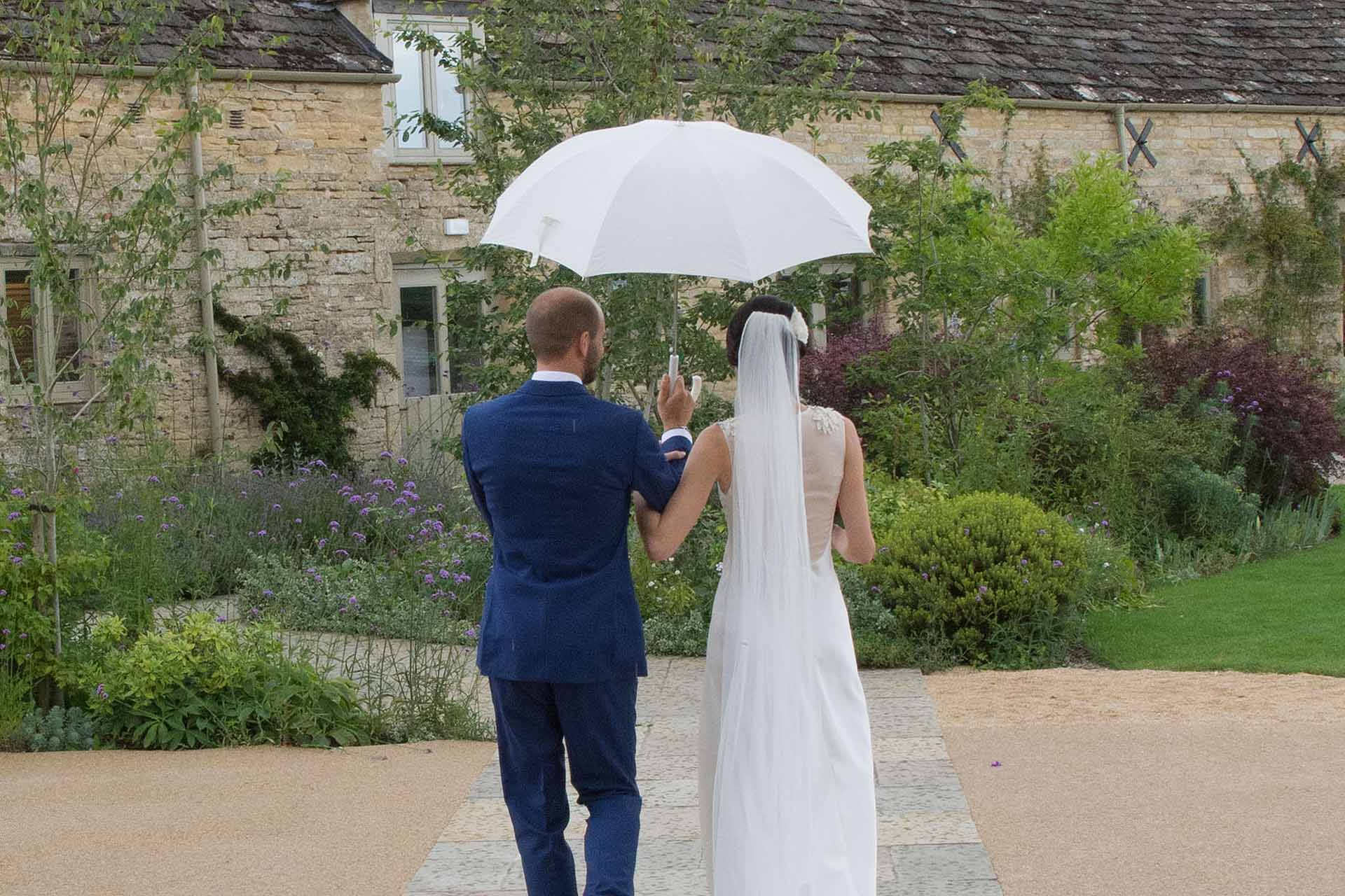 Bride and groom holding up a white umbrella