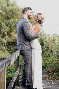 bride and groom outside on a wooden bridge