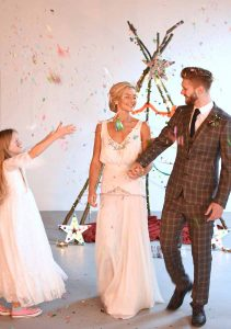 bride and groom being showered with rainbow confetti