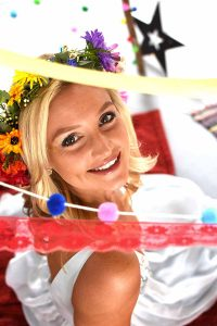 bride looking up through colourful ribbons