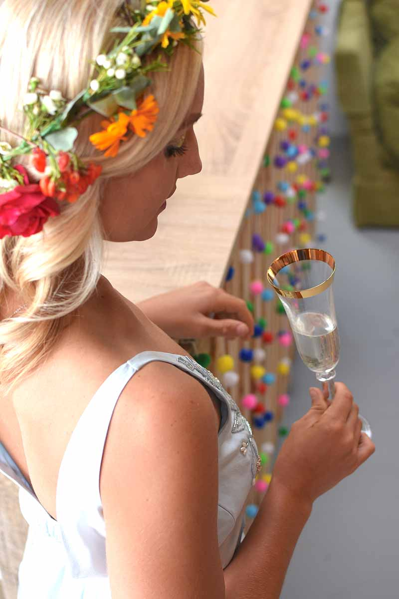 bride with rainbow flower crown looking down at gold rimed champagne flute