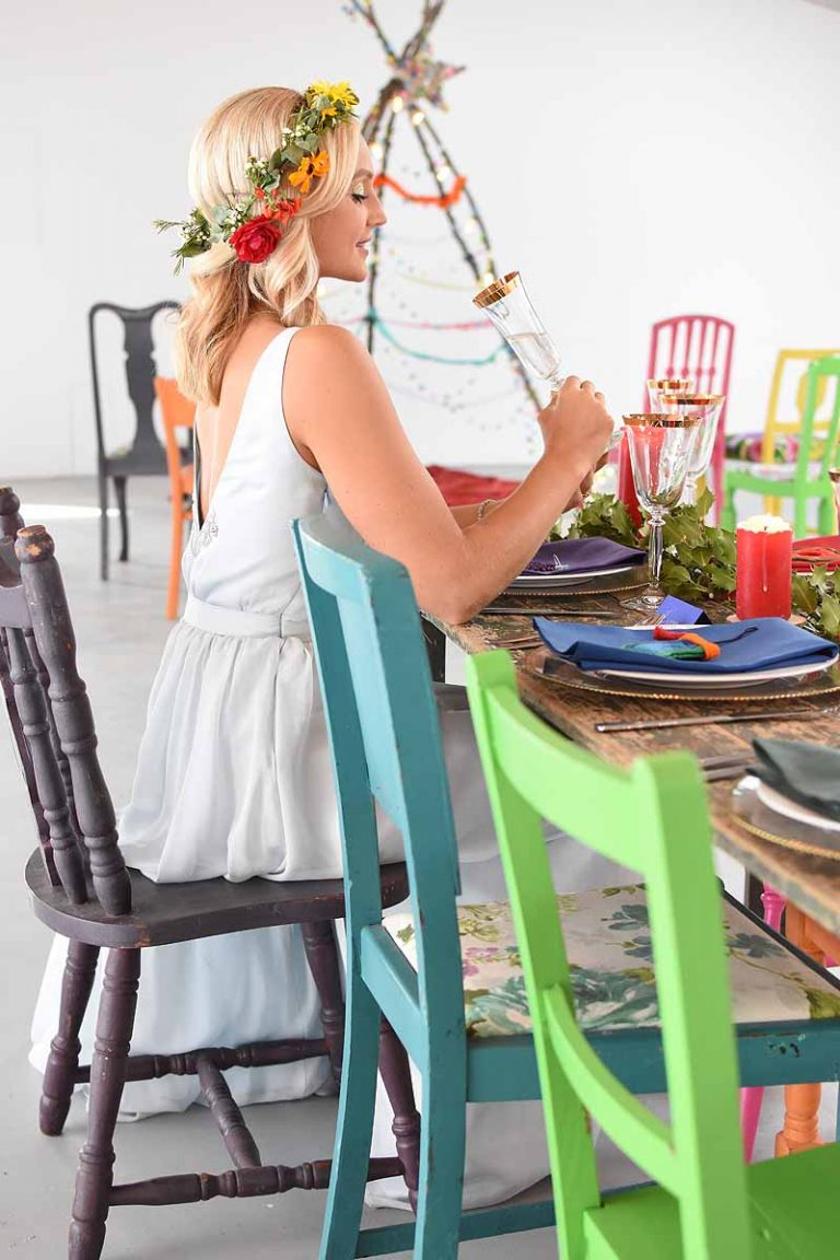 seated bride with a flower crown and colourful chairs