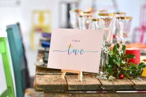Rainbow table two sign and gold rimed champagne flutes