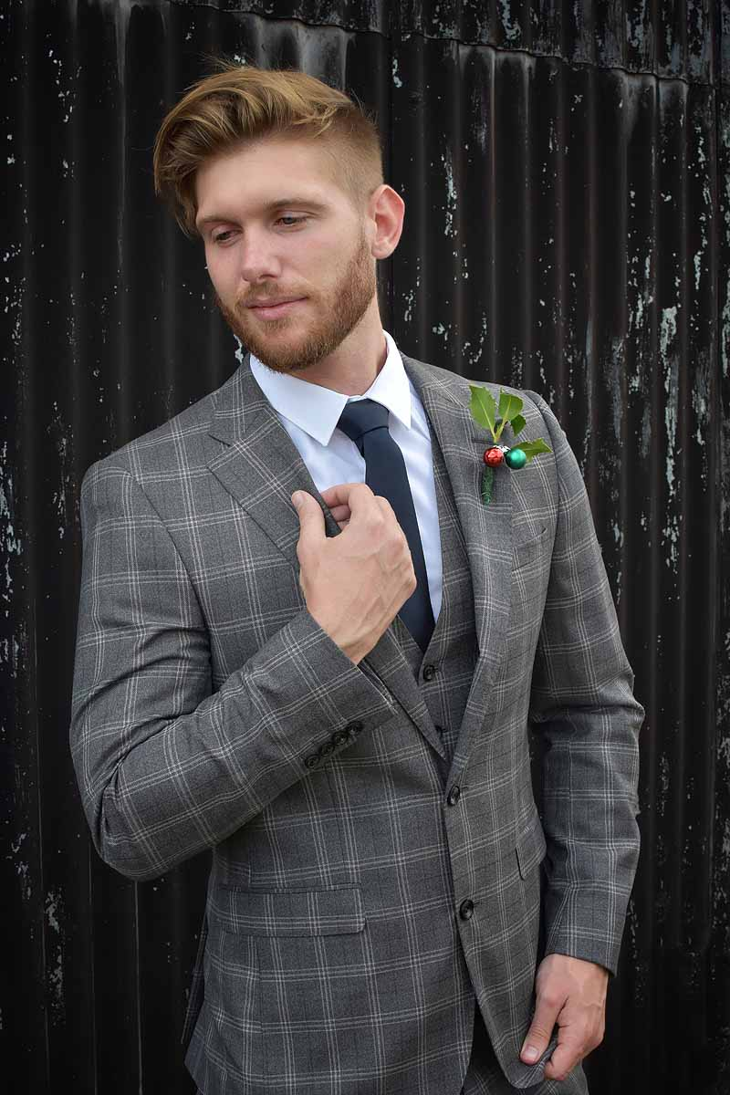 groom in grey checked suit with a black tie